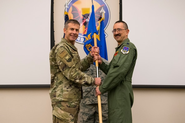 Col. Sean Carpenter, 926th Wing commander, hands the 926th Aerospace Medicine Squadron's guidon to Lt. Col. Larry Yu, 926th AMDS commander, during a change of command ceremony Oct. 20, 2019 at Nellis Air Force Base, Nevada.