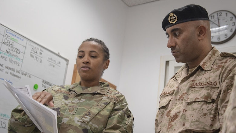 U.S. Air Force Master Sgt. Yaneesa Simpson, 386th Expeditionary Medical Group medical technician, explains the 9-line medevac request process to Kuwait army Col. Nawaf Jandoul Al-Dousari, North Military Medical Complex director, during his tour of the 386th EMDG clinic at Ali Al Salem Air Base, Kuwait, Oct. 16, 2019. The Kuwait army directors of the North Military Medical Complex visited the 386th EMDG clinic to tour the facility, share ideas on improving medical care and discuss strengthening interoperability. (U.S. Air Force photo by Tech. Sgt. Daniel Martinez)