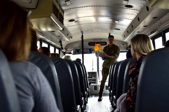 Individuals recieve a briefing inside a bus with rows of seats. The briefer is holding a yellow oxygen bag for demonstration purposes.
