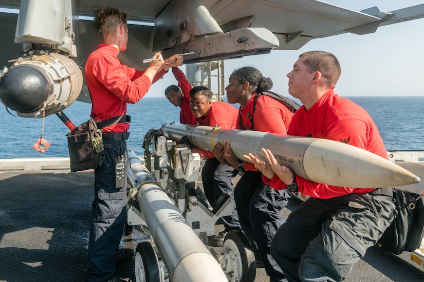 Sailors lift ordnance into a military jet.