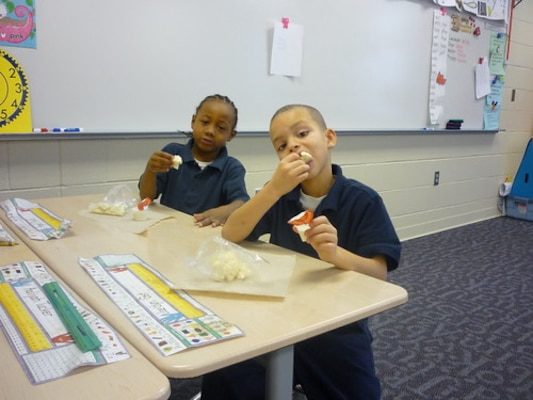 Students at E. J. Brown Elementary School in Dayton, Ohio, eat cauliflower with low fat ranch dip, as part of their school's Fresh Fruit and Vegetable Program. This school is one of the 45,000 schools that receives fresh fruits and vegetables through a partnership between DLA Troop Support and the USDA National School Lunch program. (Courtesy Photo by United States Department of Agriculture)