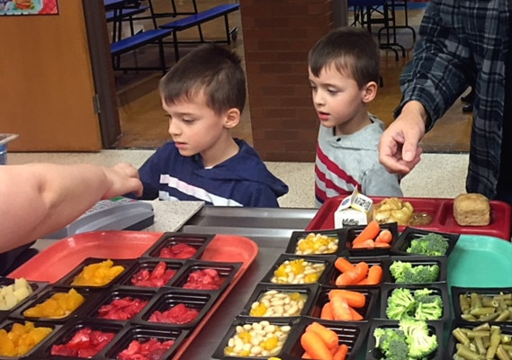 Two students proceed through the lunch line at Sayre School District in Pennsylvania. This school is one of the 45,000 schools that receives fresh fruits and vegetables through a partnership between DLA Troop Support and the USDA National School Lunch program. (Photo by Shawn Jones)