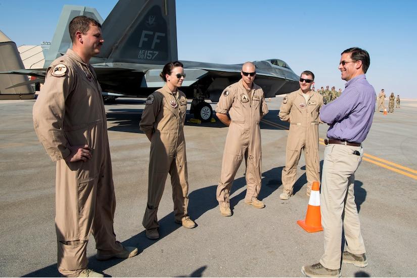 Defense Secretary Dr. Mark T. Esper talks to four airmen standing on a flightline by a plane.