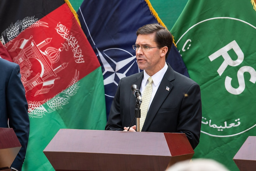 Defense Secretary Dr. Mark T. Esper speaks at podium with Afghan, NATO and Resolute Support flags behind him.