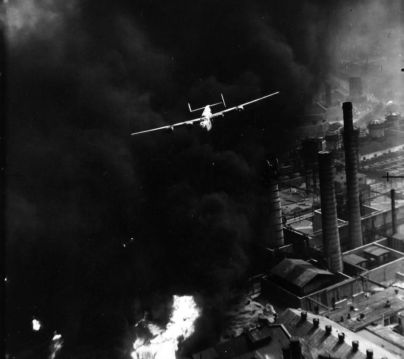 Aircraft flies over a smoking oil refinery.