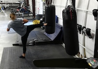 Senior Airman Stevie, 432nd Wing Staff Agency photojournalist, kicks a heavy bag in the Reaper Fitness Center at Creech Air Force Base, Nevada, Oct. 16, 2019. Equipment available for use 24/7 includes a boxing ring and Alpha Warrior Course. (U.S. Air Force photo by Airman 1st Class William Rio Rosado)