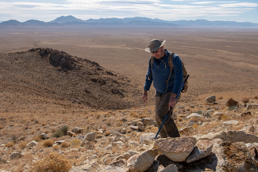 Steve Stocking, lead herpetologist with Colorado State University, scans the hillside for rattlesnakes on the Nellis Test and Training Range, Nevada, Oct. 17, 2019. Stocking partners with the 99th Civil Engineer Squadron to conduct reptile surveys at known rattlesnake den sites. (U.S. Air Force photo by Staff. Sgt. Tabatha McCarthy)