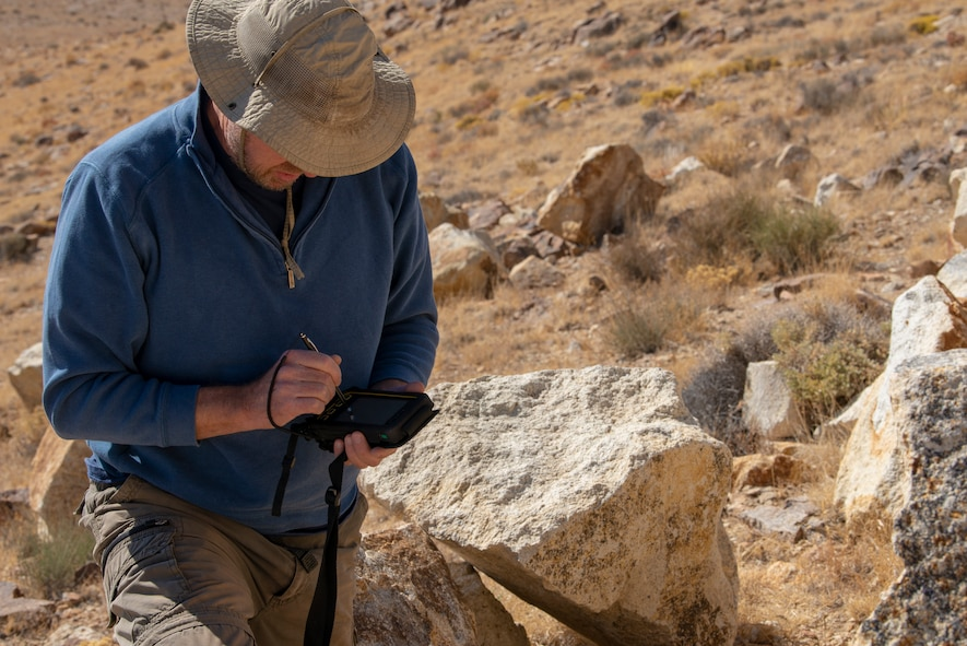 Steve Stocking, lead herpetologist with Colorado State University, documents the GPS coordinates for a rattlesnake on the Nellis Test and Training Range, Nevada, Oct. 17, 2019. The coordinates are used for the wildlife biologists to be able to find the reptiles and their dens when they go back to the sites. (U.S. Air Force photo by Staff. Sgt. Tabatha McCarthy)