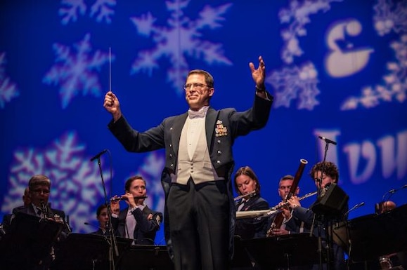 Lt. Col. Daniel Price turns to the audience during a holiday concert to conduct the audience in singing along with the Concert Band.  Academy Band musicians perform under a huge blue screen covered in snowflake designs behind him.