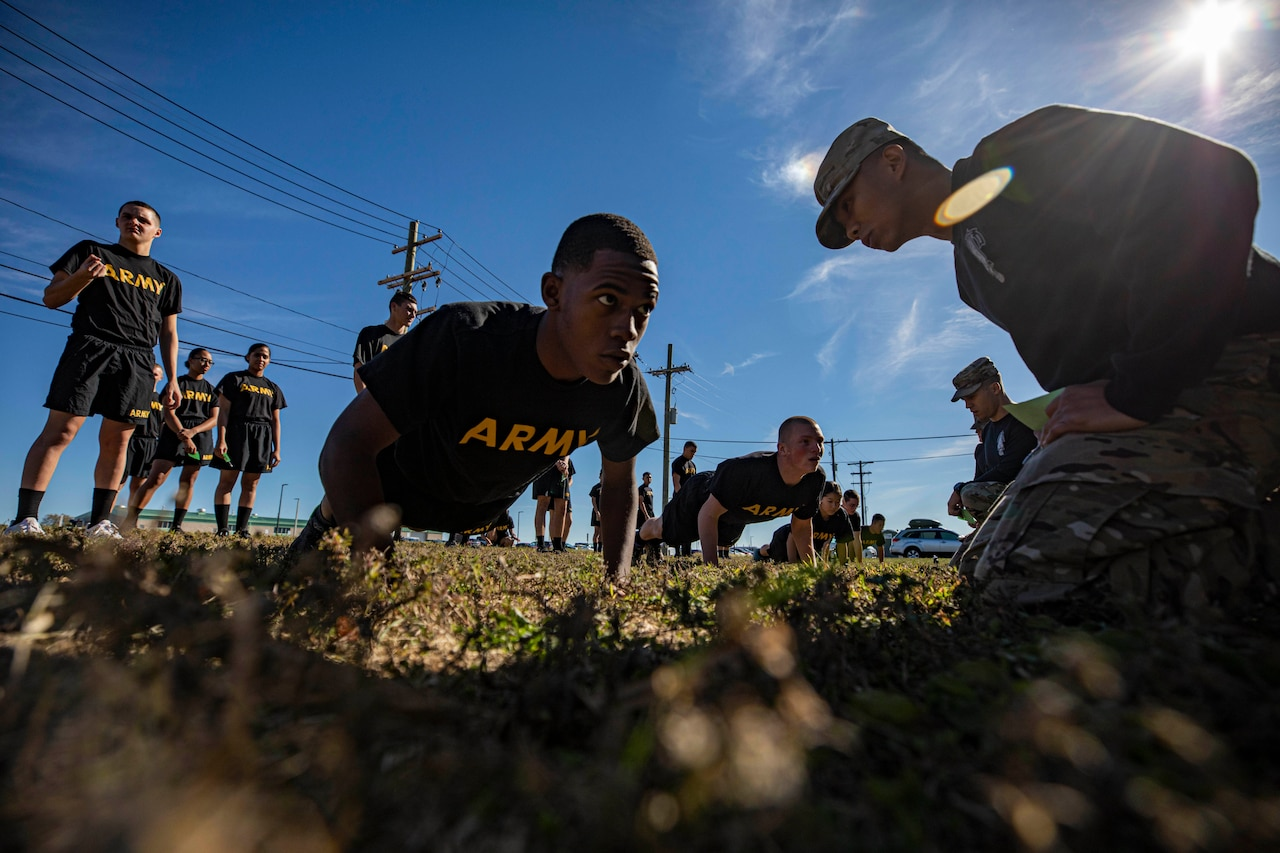 Soldiers do pushups while others stand around.