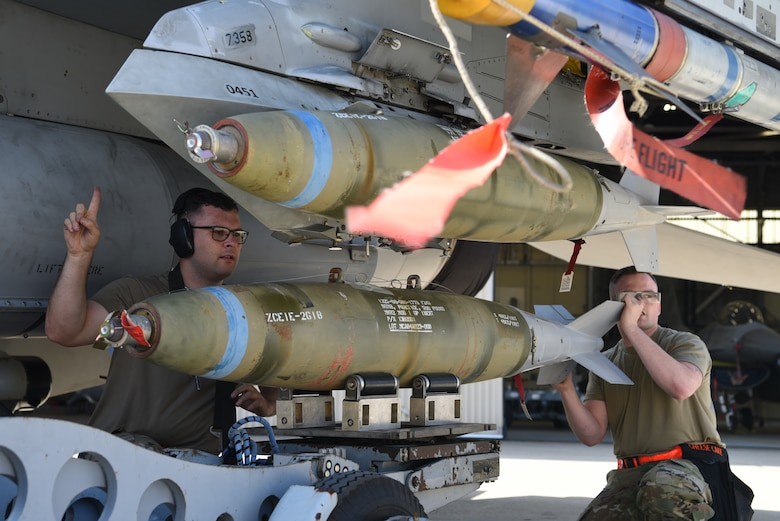 Members of the 25th Aircraft Maintenance Unit, Osan Air Base, Republic of Korea, lift a bomb during the 2019 Penn Fest competition at Kunsan Air Base, Republic of Korea, Oct. 19. 2019, The 25th AMU finished loading their aircraft the quickest and won the load crew competition overall. (U.S. Air Force photo by Staff Sgt. Joshua Edwards)