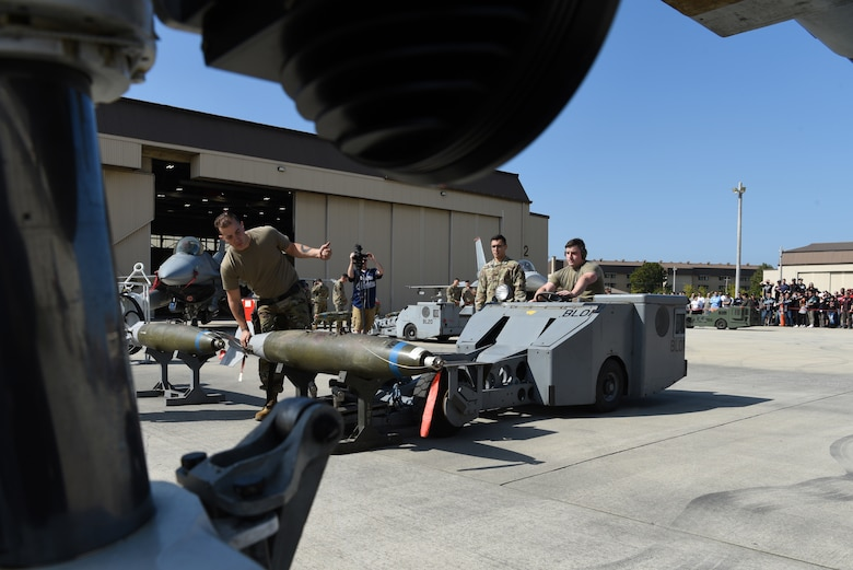Members of the 36th Aircraft Maintenance Unit, Osan Air Base, Republic of Korea, load a bomb onto an F-16 Fighting Falcon aircraft during the 2019 Penn Fest competition at Kunsan Air Base, ROK, Oct. 19, 2019. The 38th FG AMU competed against four U.S. Air Force teams and completed their loads with the second quickest times. (U.S. Air Force photo by Staff Sgt. Joshua Edwards)