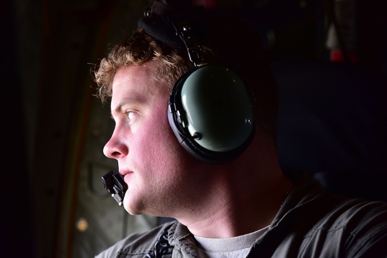 A loadmaster looks out the window of a C-130.