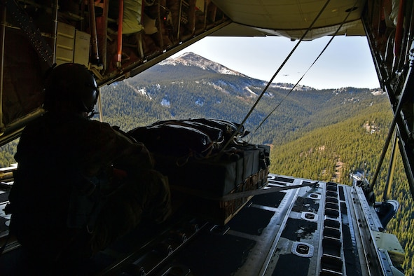 A loadmaster sits on the back of a C-130.