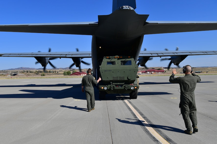 Loadmasters guide a HIMARS onto a C-130.
