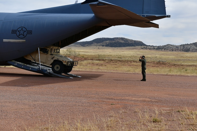 A loadmaster guides a humvee out the back of a C-130.