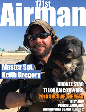 Master Sergeant Keith Gregory poses with a dog during a deployment to Afghanistan
