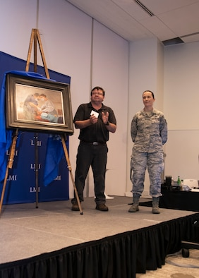 Tech Sgt. Kat Justen (right), Heritage and Combat Artist, Office of History and Heritage, Air Force Reserve Command, stands by during an art unveiling Sept. 19, 2019, at Tyson's Corner, Va. Justen's art portrayed Col. Clifford Zdanowicz, Jr., a dentist and 512th Aerospace Medicine Squadron Commander at Dover AFB