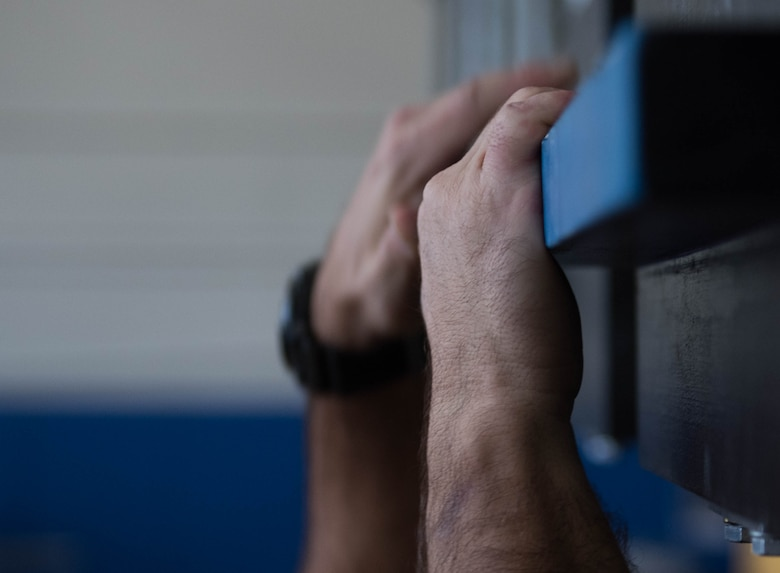 A U.S. Air Force Physical Training Leader from Joint Base Langley-Eustis, Virginia, grips the bars of the Battle Rig at the Air Combat Command gym at JBLE Oct. 17, 2019.
