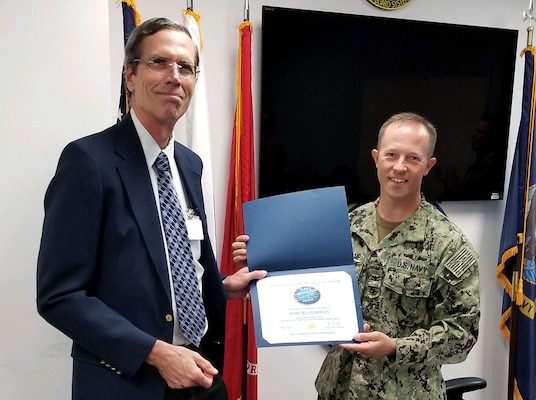 Man wearing a navy blue suit receives a certificate from a man wearing his Navy uniform