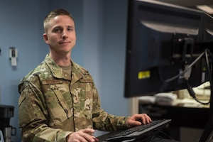 Portrait of Airman at computer looking towards to camera with hands on the keyboard