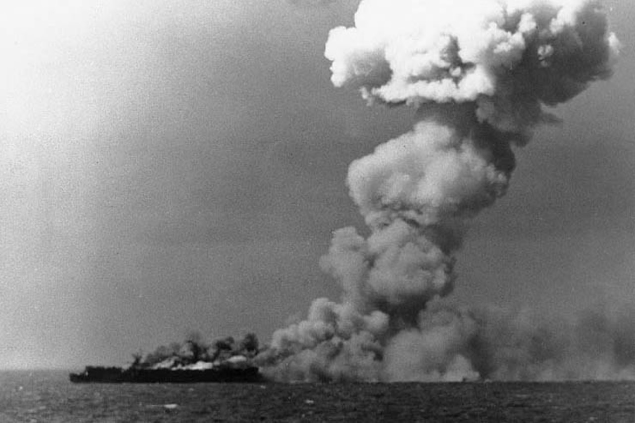 Smoke pours from an aircraft carrier.