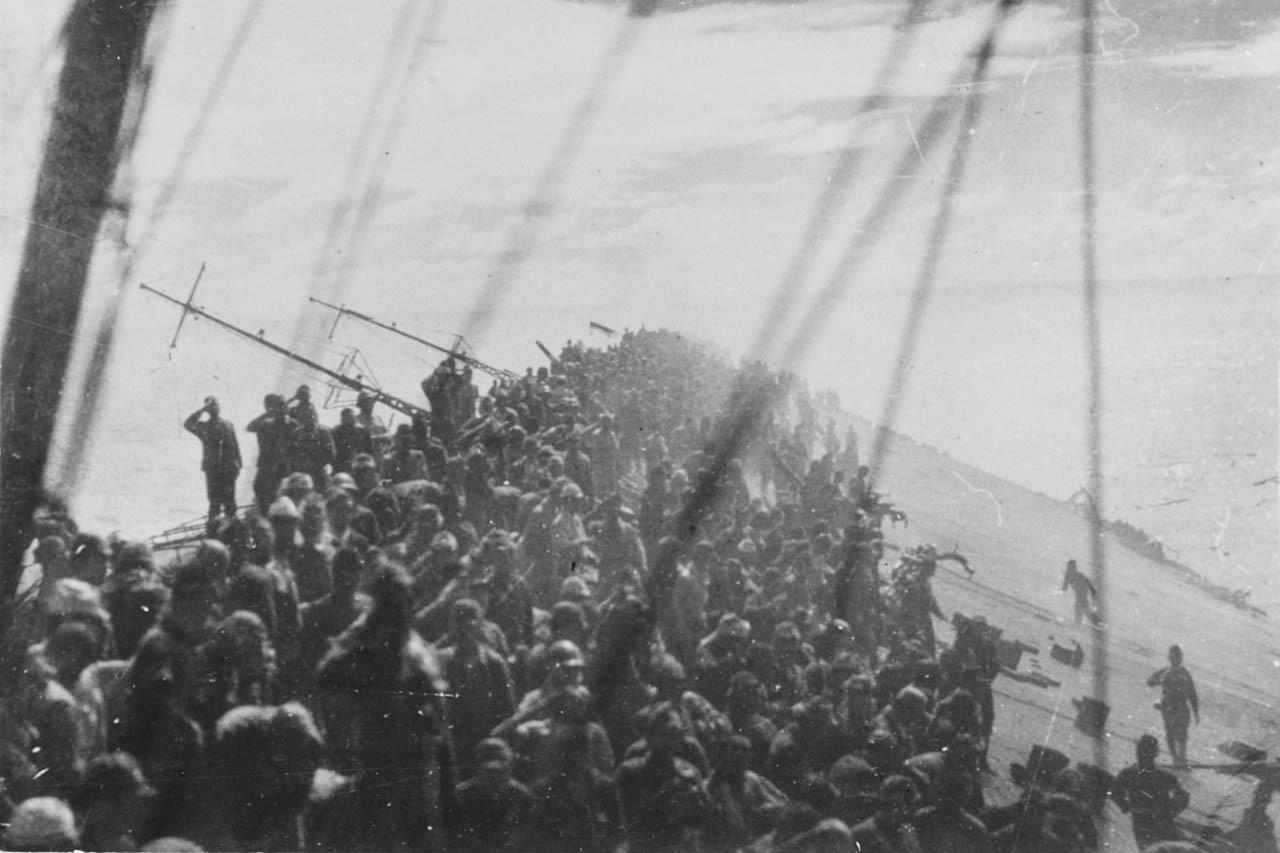 Men crowd the deck of a sinking aircraft carrier flight deck.