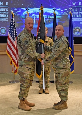 Air Force Gen. Jay Raymond, Air Force Space Command commander, left, presents colors to Army Brig. Gen James Thomas, to recognize the establishment of Joint Task Force-Space Defense during a ceremony held at Schriever Air Force Base, Colo., Oct. 21, 2019. JTF-SD will be commanded by James, who has served in space-related assignments for the past 19 years. (DoD photo by Patrick Morrow)