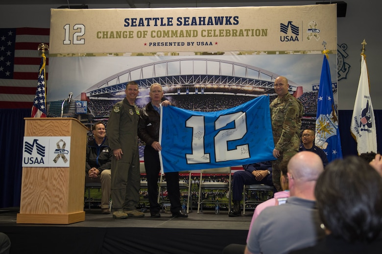 "Col. Scovill Currin, 62nd Airlift Wing commander, left, Mike Flood, Seattle Seahawks vice president of community outreach, center, and Chief Master Sgt. Rob Schultz, 62nd AW command chief, right, display the 12th Man Flag during a ""change of command"" ceremony at Coast Guard Base Seattle, Wash., Oct. 22, 2019."