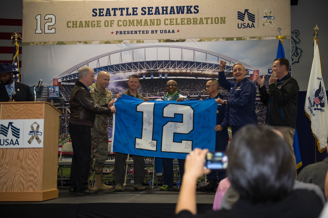 """Members of the Seattle Seahawks organization, 62nd Airlift Wing and 13 Coast Guard District hold a 12th Man Flag during a """"change of command"""" ceremony at Coast Guard Base Seattle, Wash., Oct. 22, 2019."""