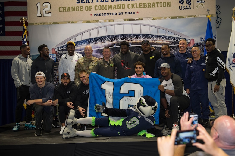 Seattle Seahawks players pose with leadership from the 62nd Airlift Wing and the 13th Coast Guard District at Coast Guard Base Seattle, Wash., Oct. 22, 2019.