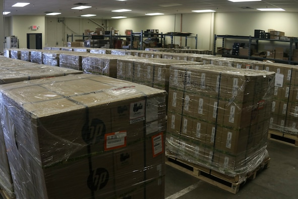 Photo shows multiple pallets with boxed laptops in a storage unit.