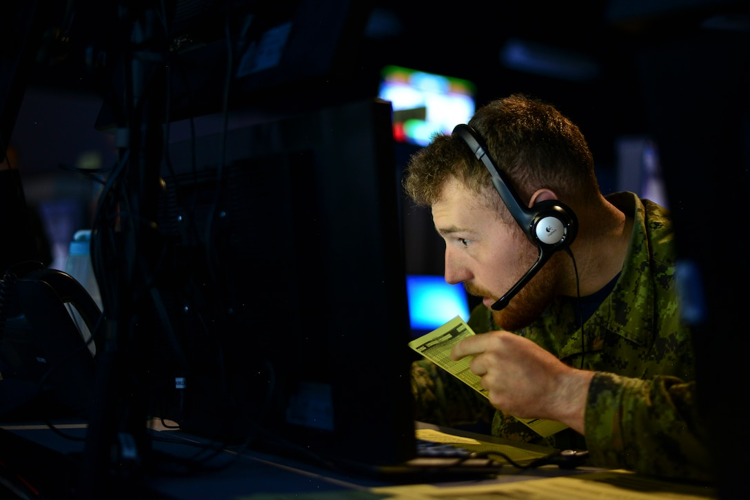 A member of the Royal Canadian Air Force takes part in the Exercise Coalition VIRTUAL FLAG 19-4 at Kirtland Air Force Base, N.M., Sept. 10, 2019. The synthetic battle spaces used numerous simulators to connect to 88 systems and 23 sites around the world, synchronizing multi-domain DoD weapon systems along with coalition partners including Canada, The United Kingdom and Australia. (U.S. Air Force photo by Staff Sgt. Kimberly Nagle)