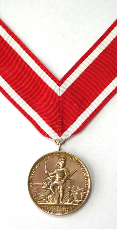 """The de Fleury Medal was the first Congressional Medal struck, if not the first medal authorized. The front of the medal says """"A Memorial and Reward for Courage and Boldness"""" in Latin, with a helmeted soldier standing amidst the ruins of a fort, holding in his right hand an unsheathed sword, and in his left the staff of the enemy's flag, which he tramples underfoot. On the reverse, again in Latin, it says: """"Fortifications, Marshes, Enemies Overcome"""" and in the center is the fortress at Stony Point with both turrets and a flag flying. At the base of the hill are two shore batteries, one of which is firing at one of six vessels on the Hudson River. Beneath the fort is the legend: """"Stony Point Carried by Storm, July 15, 1779."""""""