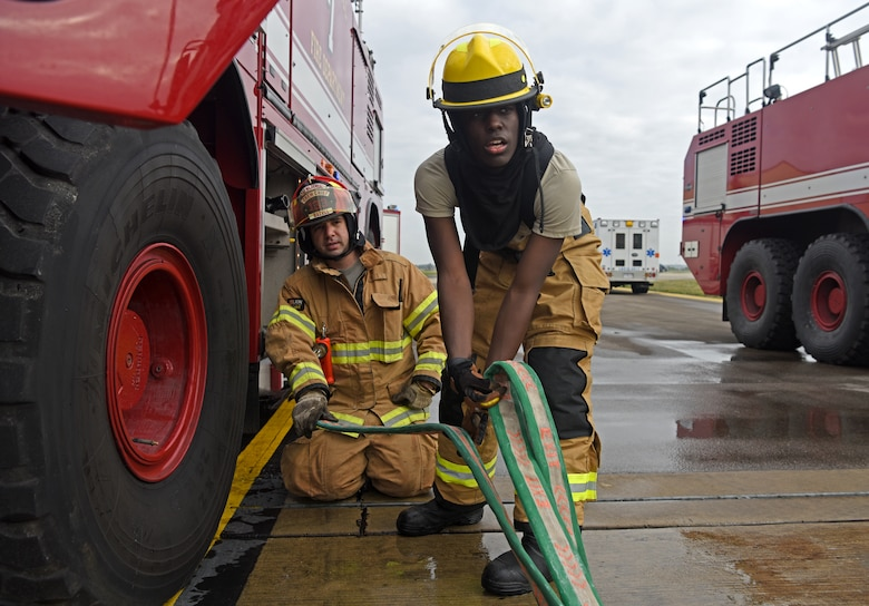 Firefighters with the 100th Civil Engineer Squadron secure a hose during a training exercise simulating a cockpit fire aboard a KC-135 Stratotanker at RAF Mildenhall, England, Oct. 22, 2019. Hands-on training is performed quarterly by the fire department to help keep firefighters familiar with the interior layout of the aircraft and proper shut-down procedures. (U.S. Air Force photo by Senior Airman Brandon Esau)