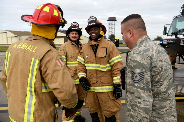 """Firefighters with the 100th Civil Engineer Squadron take a break and a have a laugh after training simulating a cockpit fire aboard a KC-135 Stratotanker at RAF Mildenhall, England, Oct. 22, 2019. The firefighters had to search for """"unaccounted personnel"""" in and around the aircraft during the simulated fire. (U.S. Air Force photo by Senior Airman Brandon Esau)"""
