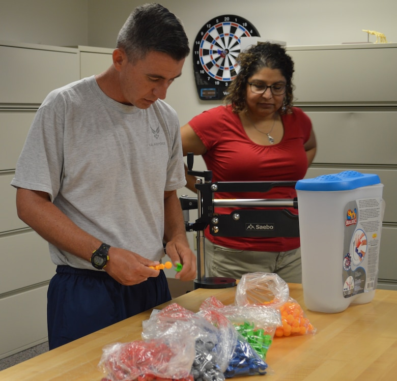 Air Force 1st Lt. Jason Hibbetts tries to connect different shaped pieces together as part of his occupational therapy Aug. 13 at the Brain Injury Rehabilitation Service at Brooke Army Medical Center at Joint Base San Antonio-Fort Sam Houston, as occupational therapist Marina LeBlanc looks on. The BIRS provides comprehensive outpatient neurorehabilitation for service members, family members and military retirees who are recovering from a stroke or other brain injuries using an interdisciplinary approach including physical therapy, occupational therapy, speech language pathology, recreational therapy, psychology, neuropsychology and case management. (Photo by Lori Newman)