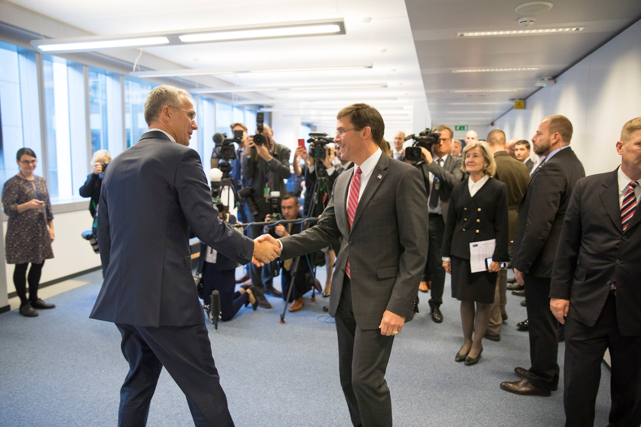 Two men shake hands in front of a large number of reporters.
