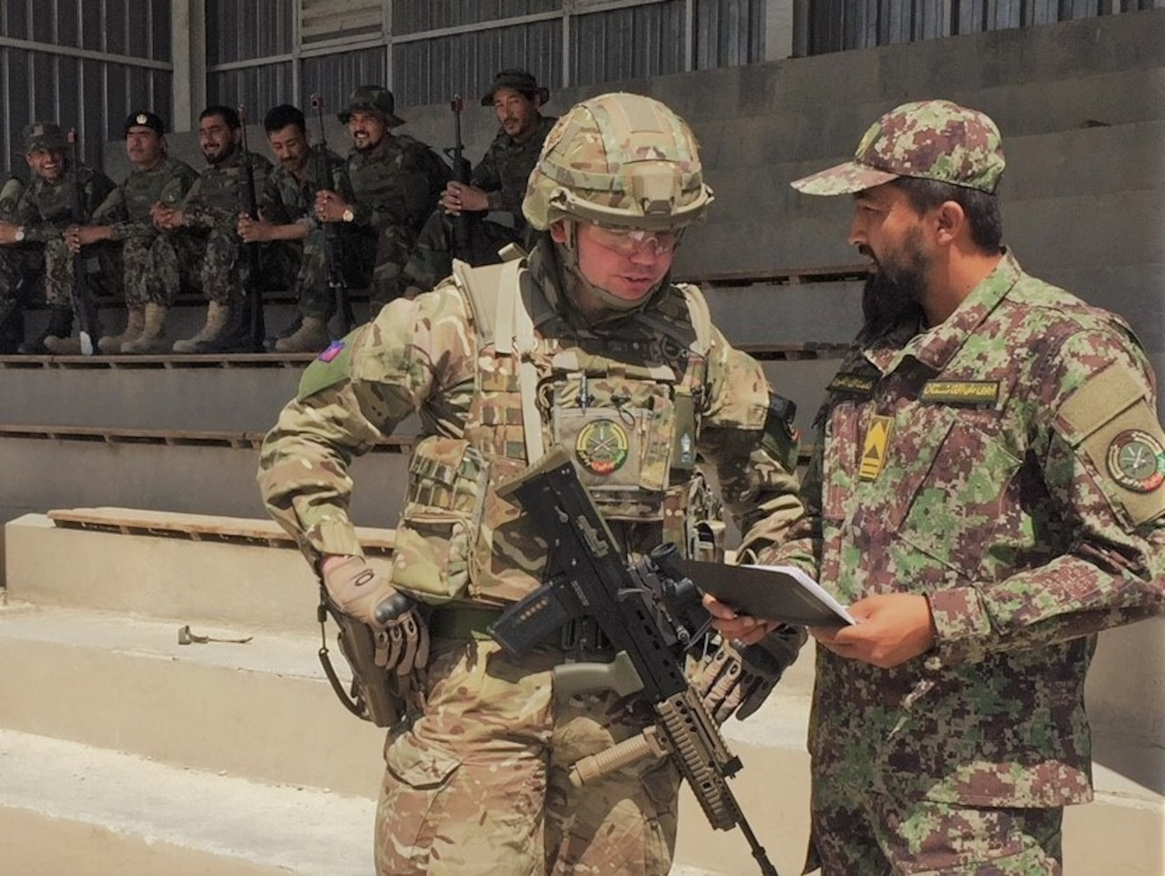 Afghan soldier speaks with British advisor.