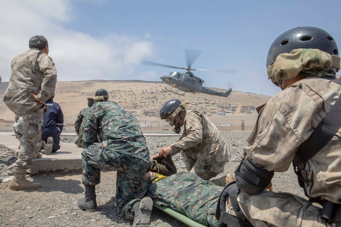 Military personnel practice medical evacuations as a helicopter flies in the background.