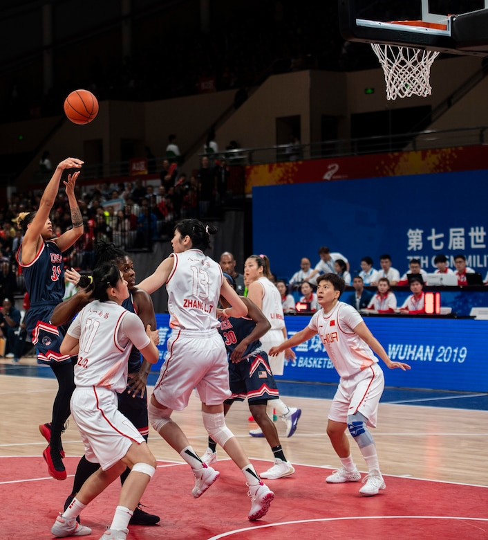 Basketball player launches a jump shot amid four defenders.