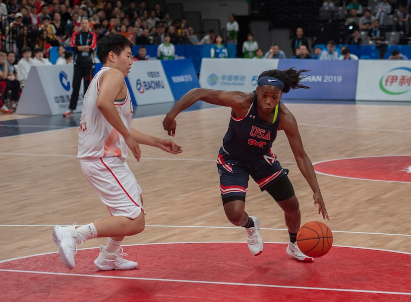 Basketball player drives the lane against a defender.