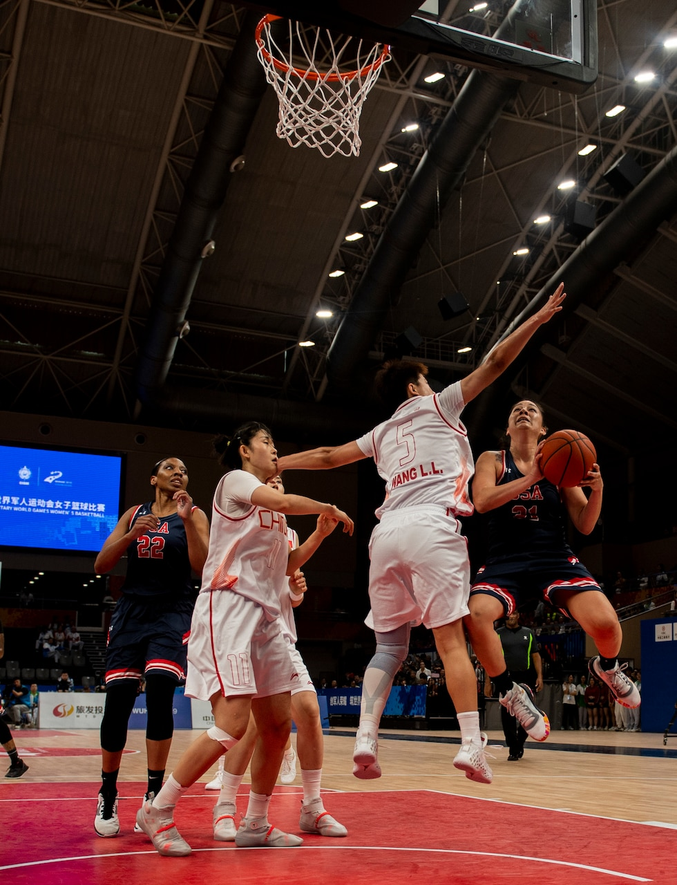 Basketball player holding the ball jumps to make a shot, closely guarded by a defender.