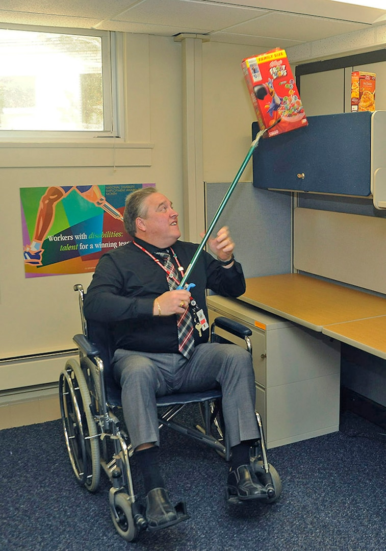 DLA Logistics Information Services Director Ray Zingaretti navigates cubicle life at the wheelchair users station.