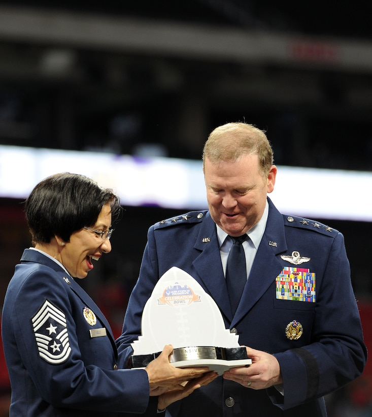 U.S. Air Force Chief Master Sgt. Ericka Kelly, Command Chief, Air Force Reserve Command and U.S. Air Force Lt. Gen. Richard W. Scobee, Commander, AFRC, hold the Offensive Most Valuable Player Award for the Air Force Reserve Celebration Bowl before presenting it to the recipient at the conclusion of the game at Mercedes-Benz Stadium in Atlanta, Georgia, December 15, 2018. (U.S. Air Force photo by Master Sgt. Stephen D. Schester)