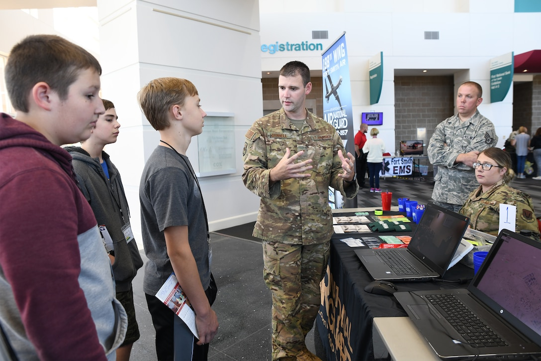 Staff Sgt. Ryan Grinnell, an intelligence analyst with the 123rd Intelligence Squadron, demonstrates a computer simulation of an intelligence, surveillance, and reconnaissance mission to area junior high students at the Fort Smith Public Schools' ICan Career Expo, held Oct. 22, 2019, in Fort Smith, Arkansas. The 188th Wing's mission combines ISR, remotely piloted aircraft and targeting to serve state and national military objectives. (U.S. Air National Guard photo by Tech. Sgt. John E. Hillier)