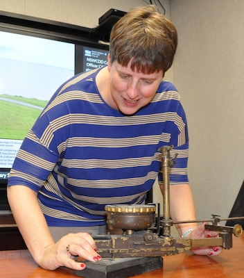 "IMAGE: DAHLGREN, Va. (Oct. 24, 2019) – Bonnie Roman, Naval Surface Warfare Center Dahlgren Division (NSWCDD) management analyst, examines a World War I bombsight. The aircraft course-setting bombsight is one of the few surviving examples of the many bombsights tested at Naval Proving Ground Dahlgren in the 1920s and 1930s. Roman – who serves as the NSWCDD Integrated Budget Planning and Execution System lead - is the command employee featured for October 2019 NSWCDD National Disability Employment Awareness Month. ""Most people I have interactions with don't realize that I am deaf in my right ear since I have adapted to losing my hearing as a child,"" said Roman. ""When I am not working, I love to travel to see different scenery throughout the United States and other countries."""