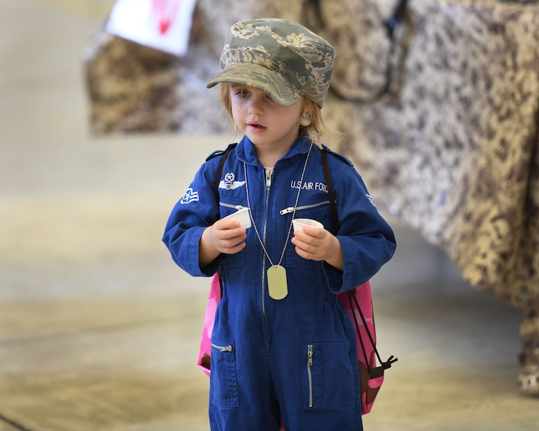 A child stands in a hangar.