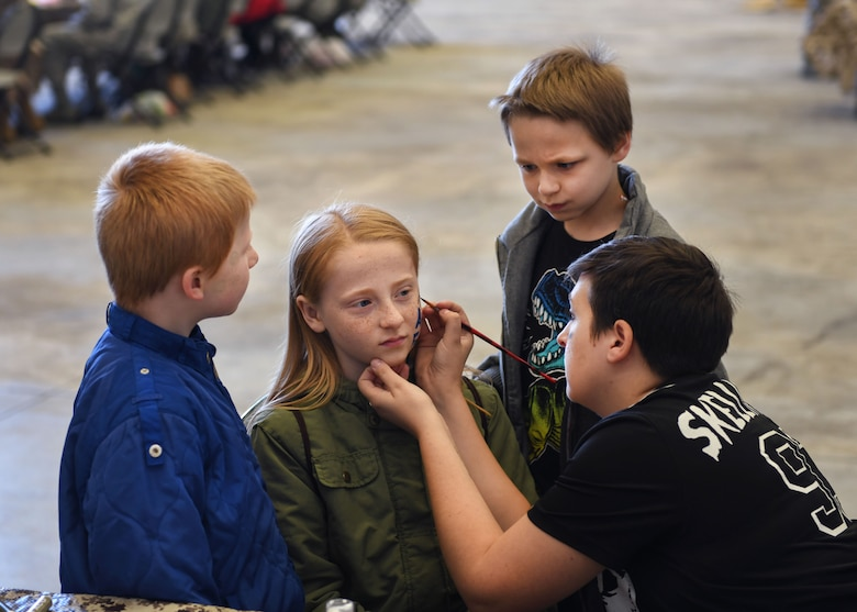 Two children watch as a girl gets her face painted by a volunteer.