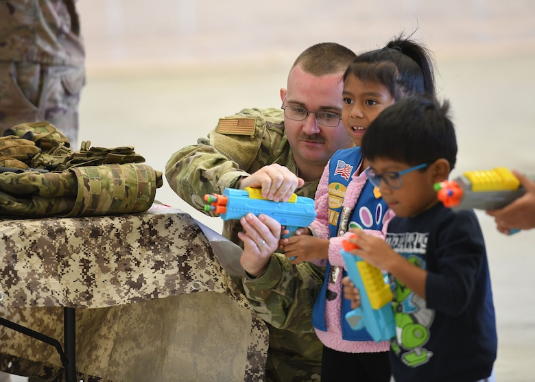 An Airman helps children with a toy.